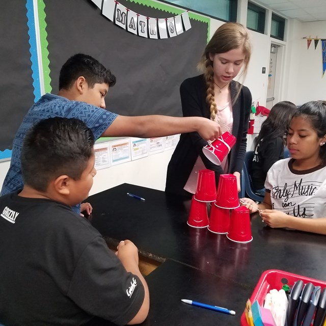 Students prepare to engage in a new experiment where they first have to stack cups together.
